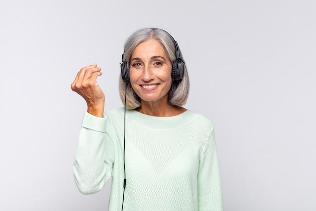 Donna di mezza età che fa gesto di capice o denaro