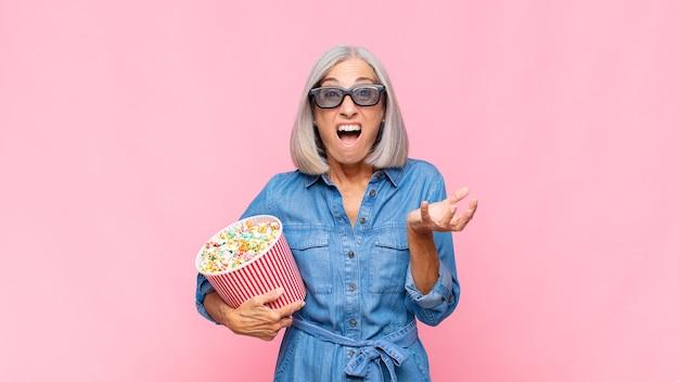 Donna di mezza età a bocca aperta e stupita, scioccata e stupita da un incredibile concetto di film a sorpresa