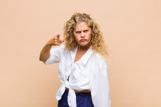 Donna di mezza età che indica alla macchina fotografica con un'espressione aggressiva arrabbiata