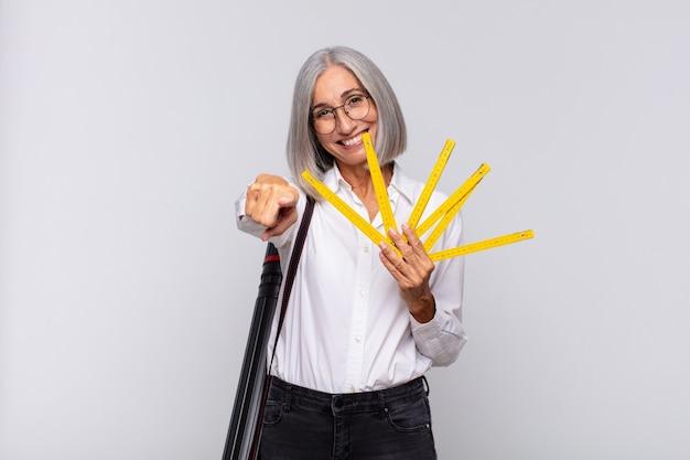Donna di mezza età che punta alla telecamera con un sorriso soddisfatto, fiducioso, amichevole, scegliendo te. concetto di architetto