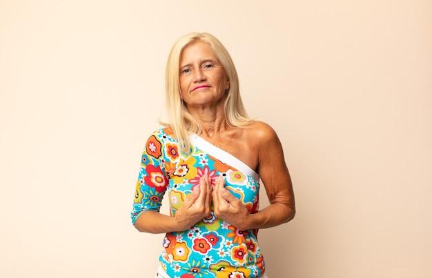 Donna di mezza età che indica se stessa con uno sguardo confuso e interrogativo, scioccata e sorpresa di essere stata scelta