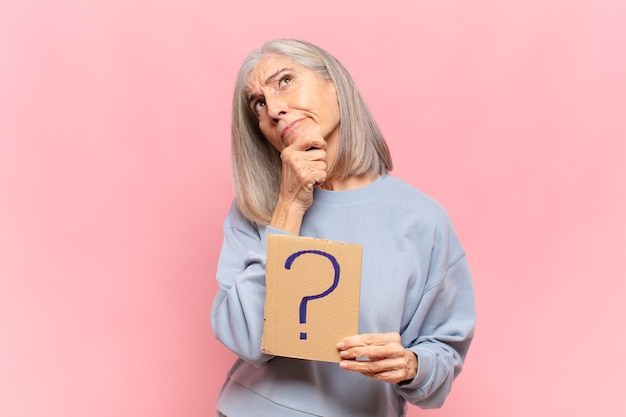 Donna di mezza età che posa con l'insegna del punto interrogativo