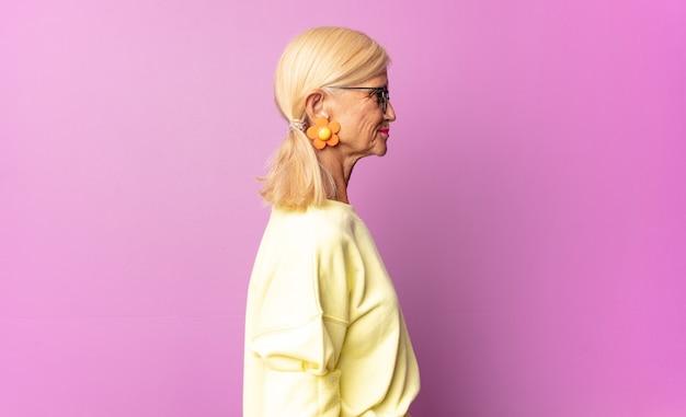 Donna di mezza età sulla vista di profilo che cerca di copiare lo spazio davanti, pensare, immaginare o sognare ad occhi aperti