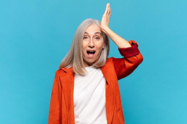 Donna di mezza età che alza il palmo alla fronte pensando oops, dopo aver commesso uno stupido errore o ricordando, sentendosi stupida