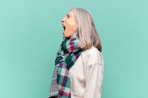 Donna di mezza età che grida furiosamente, grida in modo aggressivo, sembra stressata e arrabbiata
