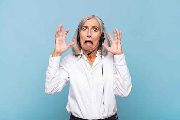 Donna di mezza età che grida con le mani in alto, sentendosi furiosa, frustrata, stressata e sconvolta. concetto di telemarketer