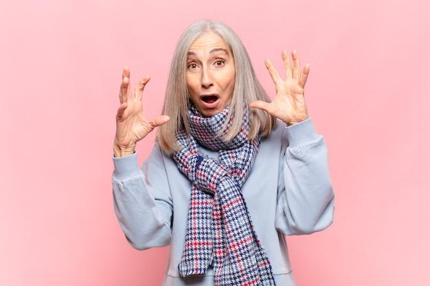 Donna di mezza età che grida con le mani in alto, sentendosi furiosa, frustrata, stressata e sconvolta