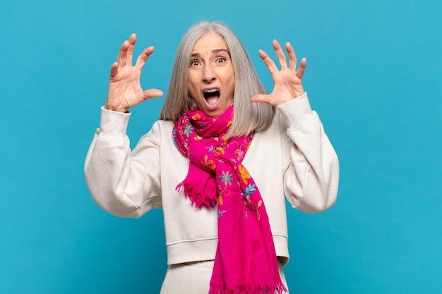 Donna di mezza età che urla con le mani in alto, sentendosi furiosa, frustrata, stressata e sconvolta