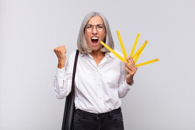 Donna di mezza età che grida in modo aggressivo con un'espressione arrabbiata o con i pugni chiusi per celebrare il successo. concetto di architetto