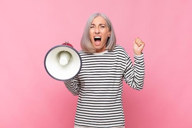 Donna di mezza età che grida in modo aggressivo con un'espressione arrabbiata o con i pugni serrati che celebra il successo con un megafono