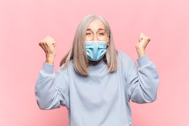 Donna di mezza età che grida in modo aggressivo con un'espressione arrabbiata o con i pugni chiusi per celebrare il successo