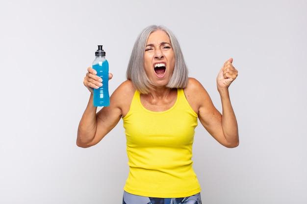 Donna di mezza età che grida in modo aggressivo con un'espressione arrabbiata o con i pugni chiusi