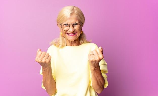 Donna di mezza età che grida trionfante, ridendo e sentendosi felice ed eccitata