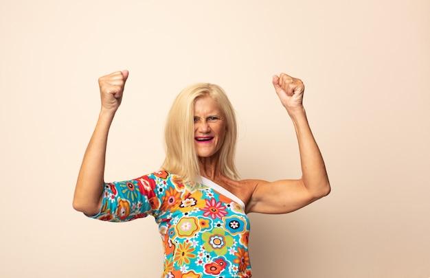 Donna di mezza età che grida trionfante, guardando come vincitore eccitato, felice e sorpreso, festeggiando