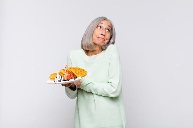 Donna di mezza età che scrolla le spalle, sentendosi confusa e incerta, dubbiosa con le braccia incrociate e lo sguardo perplesso. concetto di colazione