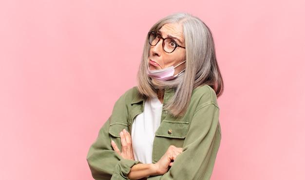 Donna di mezza età che scrolla le spalle, sentendosi confusa e incerta, dubbiosa con le braccia incrociate e lo sguardo perplesso