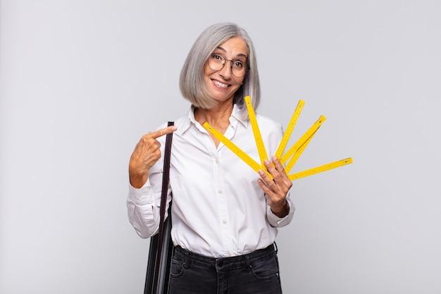 Donna di mezza età che sorride allegramente, sentendosi felice e indicando il lato e verso l'alto, mostrando l'oggetto nello spazio della copia. concetto di architetto