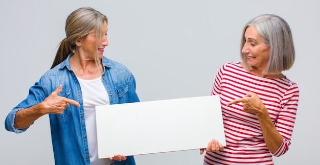 Donna di mezza età che sorride allegramente, sentendosi felice e indicando il lato e verso l'alto, mostrando l'oggetto nello spazio della copia