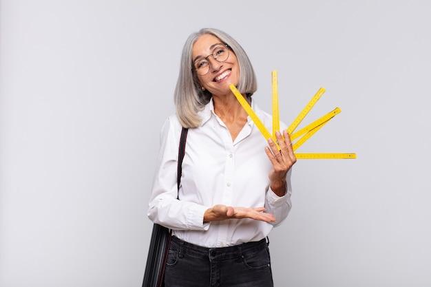 Donna di mezza età che sorride allegramente, sentendosi felice e mostrando un concetto nello spazio della copia con il palmo della mano. concetto di architetto