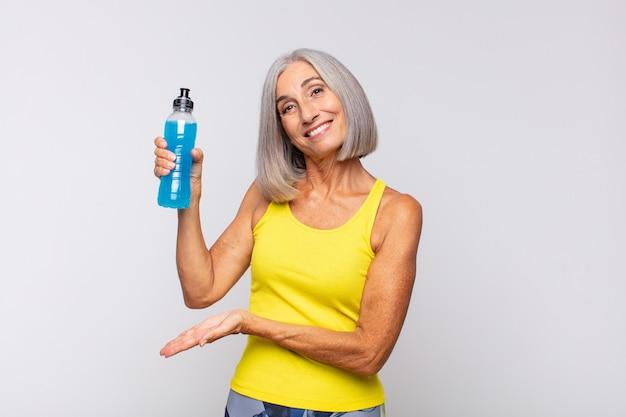 Donna di mezza età che sorride allegramente, sentendosi felice e mostrando un concetto