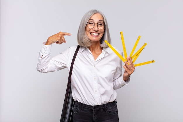 Donna di mezza età che sorride fiduciosamente indicando il proprio ampio sorriso isolato