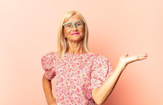 Donna di mezza età che sorride, sentendosi felice, spensierata e soddisfatta, indicando un concetto o un'idea sullo spazio della copia sul lato