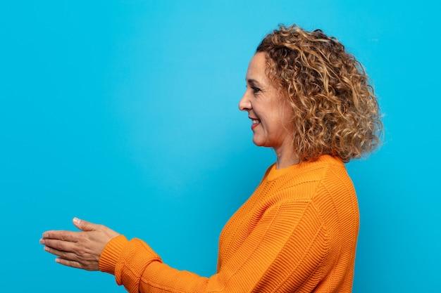 Donna di mezza età che sorride, ti saluta e ti offre una stretta di mano per chiudere un affare di successo, concetto di cooperazione