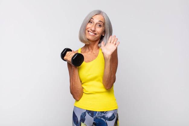 Donna di mezza età che sorride allegramente e allegramente, agitando la mano, dandoti il benvenuto e salutandoti o salutandoti. concetto di fitness