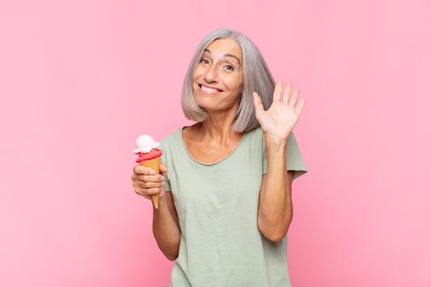 Donna di mezza età che sorride allegramente e allegramente, agitando la mano, dandoti il benvenuto e salutandoti o salutandoti con un gelato