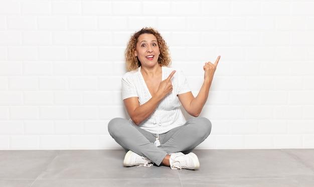 Donna di mezza età che sorride felicemente e punta a lato e verso l'alto con entrambe le mani che mostra l'oggetto nello spazio della copia
