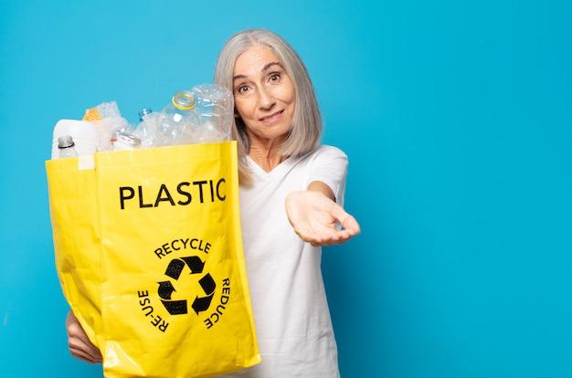 Donna di mezza età che sorride felicemente con in mano un sacchetto di riciclo amichevole e fiducioso