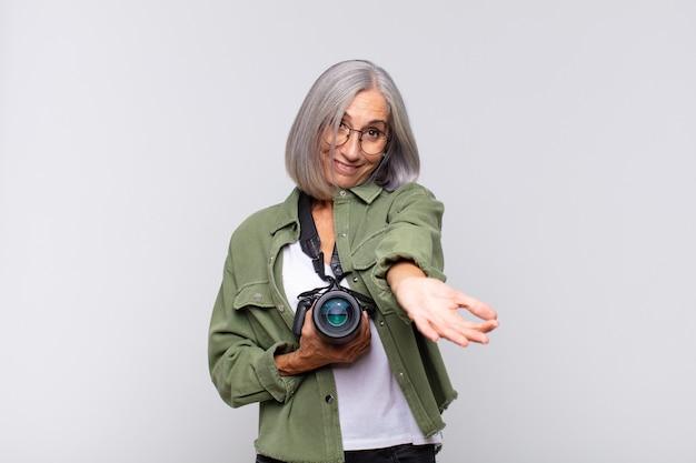 Donna di mezza età che sorride felicemente con uno sguardo amichevole, sicuro di sé, positivo, offrendo e mostrando un oggetto o un concetto. concetto di fotografo
