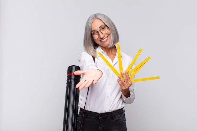 Donna di mezza età che sorride felicemente con sguardo amichevole, fiducioso e positivo