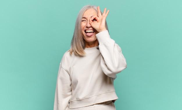 Donna di mezza età sorridente felicemente con una faccia buffa, scherzando e guardando attraverso lo spioncino, spiando i segreti