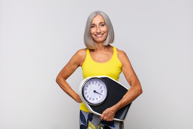 Donna di mezza età che sorride felicemente con una mano sull'anca e sicura