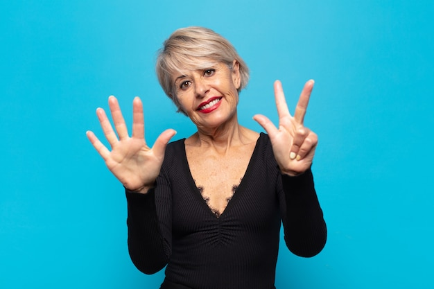 Donna di mezza età che sorride e sembra amichevole, mostrando il numero otto o ottavo con la mano in avanti, conto alla rovescia