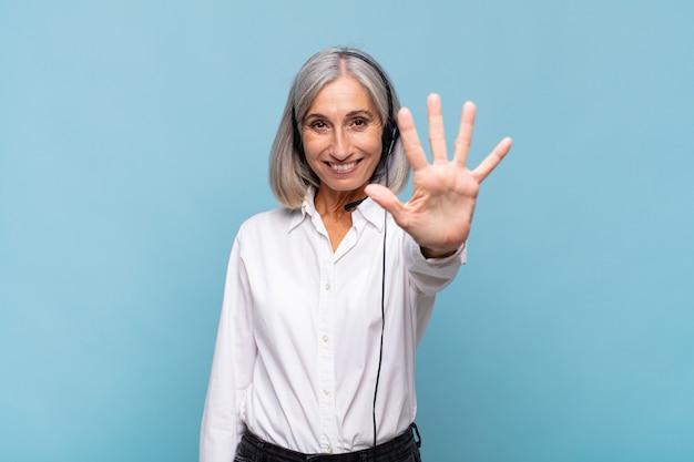 Donna di mezza età sorridente e dall'aspetto amichevole, che mostra il numero cinque o il quinto con la mano in avanti, conto alla rovescia. concetto di telemarketing