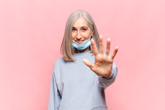 Donna di mezza età che sorride e sembra amichevole, mostrando il numero cinque o quinto con la mano in avanti, conto alla rovescia