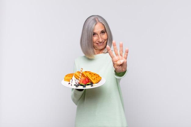 Donna di mezza età che sorride e sembra amichevole, mostrando il numero quattro o quarto con la mano in avanti, contando alla rovescia. concetto di colazione