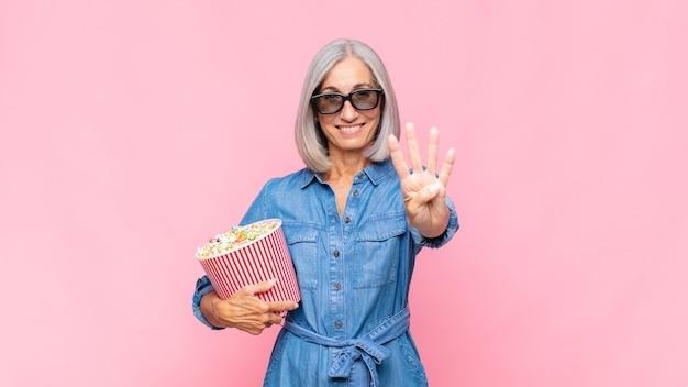 Donna di mezza età che sorride e sembra amichevole, mostrando il numero quattro o quarto con la mano in avanti, contando il concetto di film