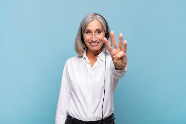 Donna di mezza età che sorride e sembra amichevole, mostrando il numero quattro o quarto con la mano in avanti, contando alla rovescia. concetto di telemarketer