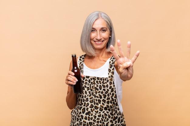 Donna di mezza età che sorride e sembra amichevole, mostrando il numero quattro o il quarto con la mano in avanti, il conto alla rovescia con una birra