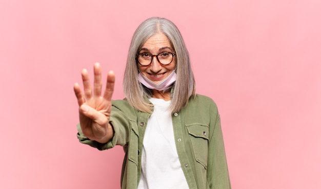 Donna di mezza età che sorride e sembra amichevole, mostrando il numero quattro o quarto con la mano in avanti, contando alla rovescia