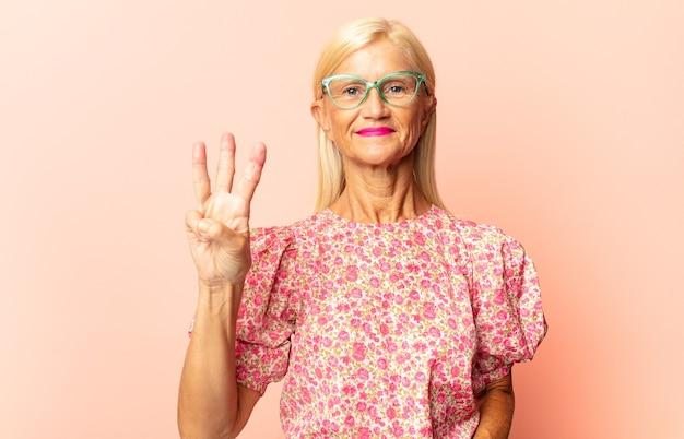 Donna di mezza età che sorride e sembra amichevole, mostrando il numero quattro o quarto con la mano in avanti