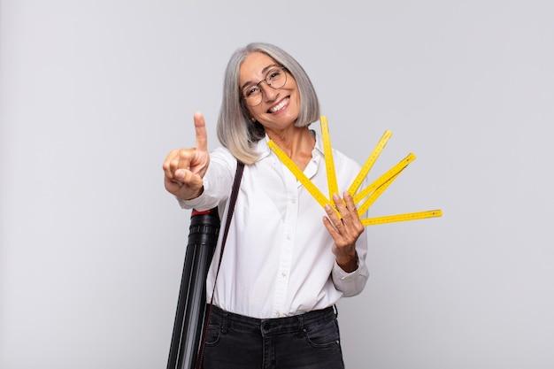 Donna di mezza età sorridente e dall'aspetto amichevole, mostrando il numero uno o il primo con la mano in avanti, conto alla rovescia. concetto di architetto