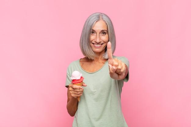 Donna di mezza età che sorride e sembra amichevole, mostrando il numero uno o il primo con la mano in avanti, contando alla rovescia avendo un gelato