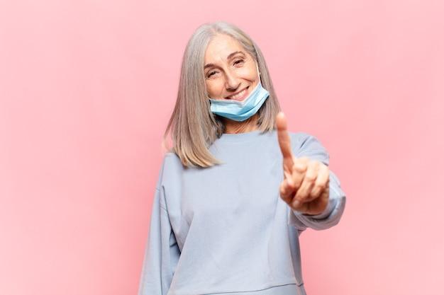 Donna di mezza età che sorride e sembra amichevole, mostrando il numero uno o il primo con la mano in avanti, il conto alla rovescia