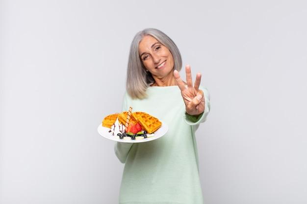 Donna di mezza età che sorride e sembra amichevole, mostrando il numero tre