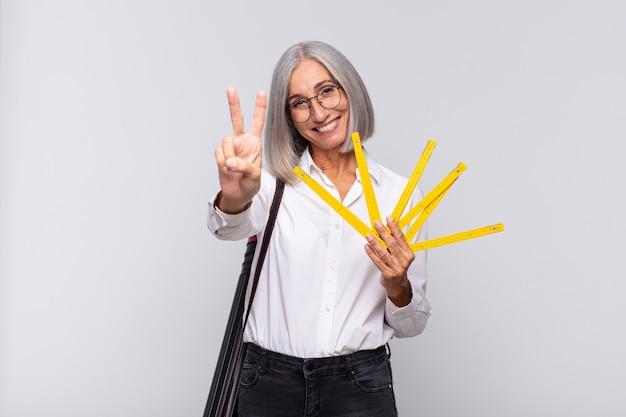 Donna di mezza età che sorride e sembra felice, spensierata e positiva, gesticolando vittoria o pace con una mano. concetto di architetto