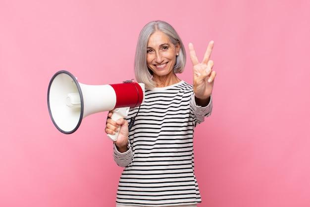 Donna di mezza età che sorride e sembra felice, spensierata e positiva, gesticolando vittoria o pace con una mano con un megafono